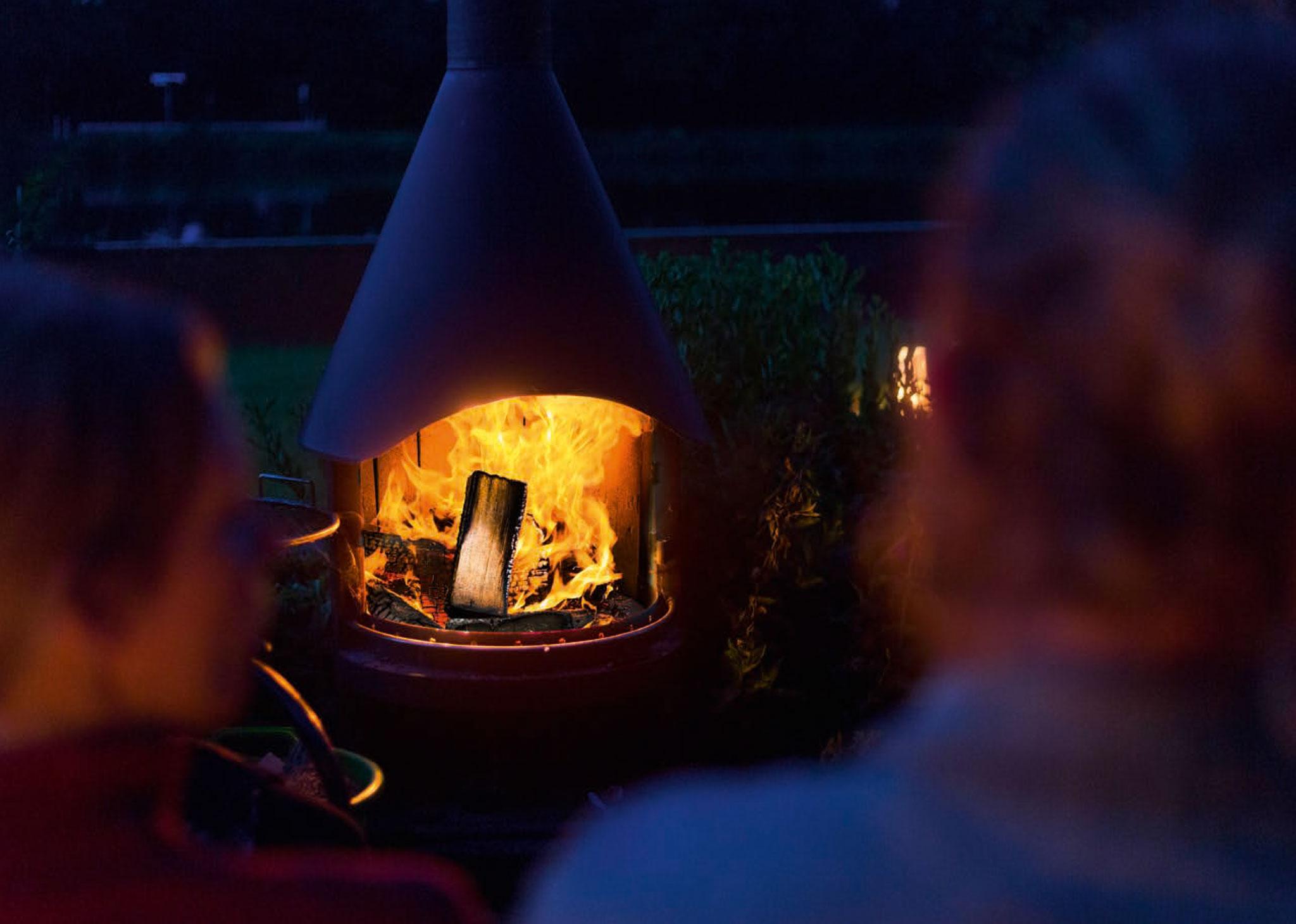 Außenkamin brennt im Garten.